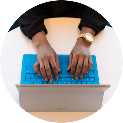 Hands typing on on laptop gold watch blue keyboard