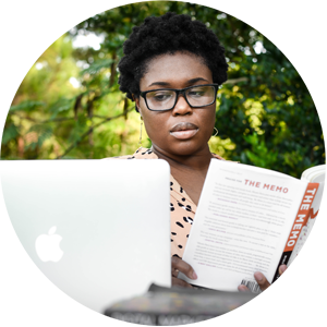 Black woman multitasking reading a book and checking her laptop