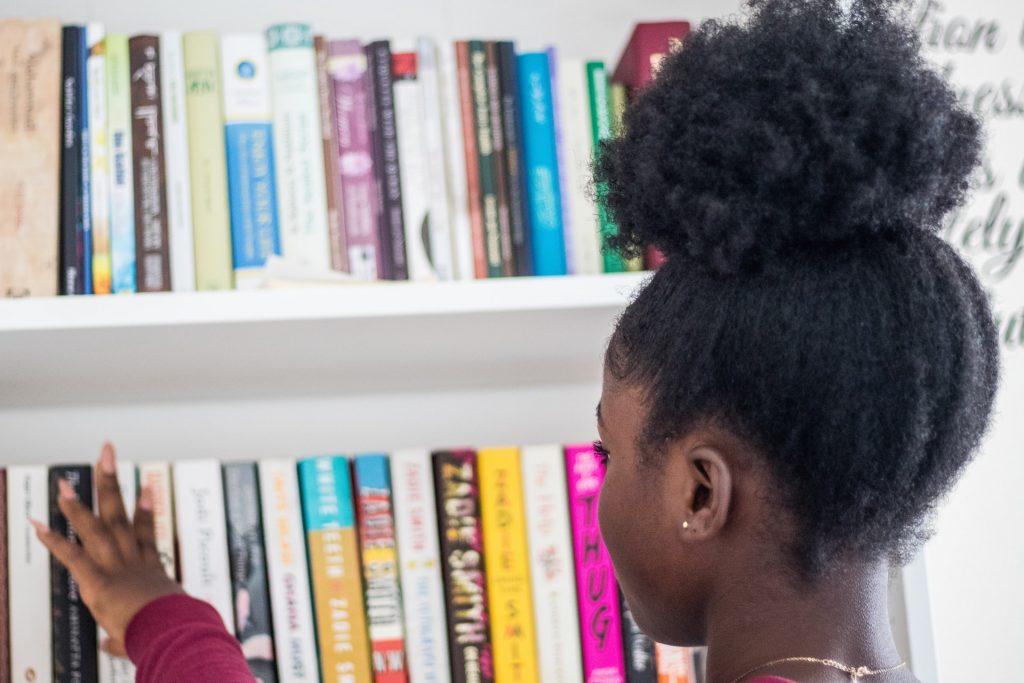 Black little girl on a library full of books