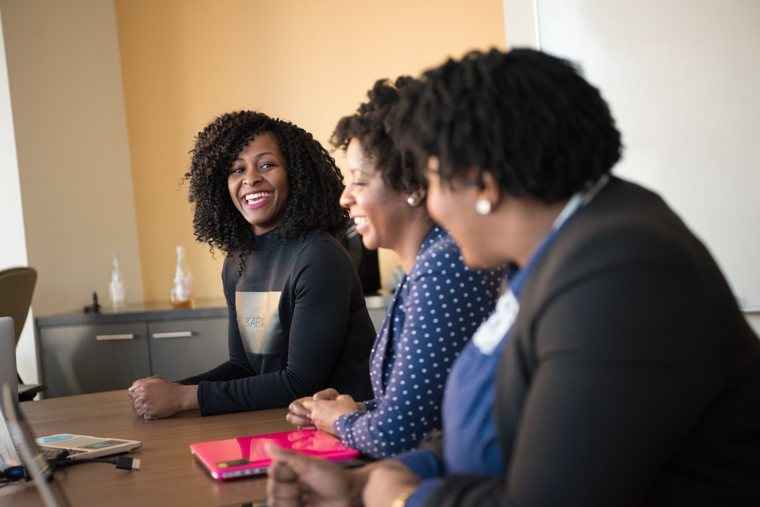 Black co-workers women laughing with each other