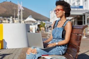 Pretty black woman watches show with earphones and notebook, enjoys high volume, listens audio book, prepares for classes, has stroll during sunny summer day, wears jean overalls, browses internet